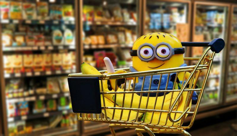 Blije minion met bananen in een boodschappenkarretje in de supermarkt