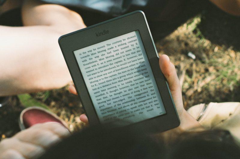 iemand die buiten op een e-reader leest