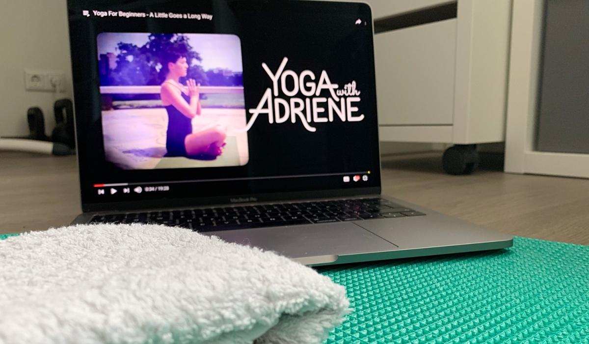 YouTube yoga doen thuis: laptop met YouTube yoga les van Yoga with Adriene, matje en handdoek
