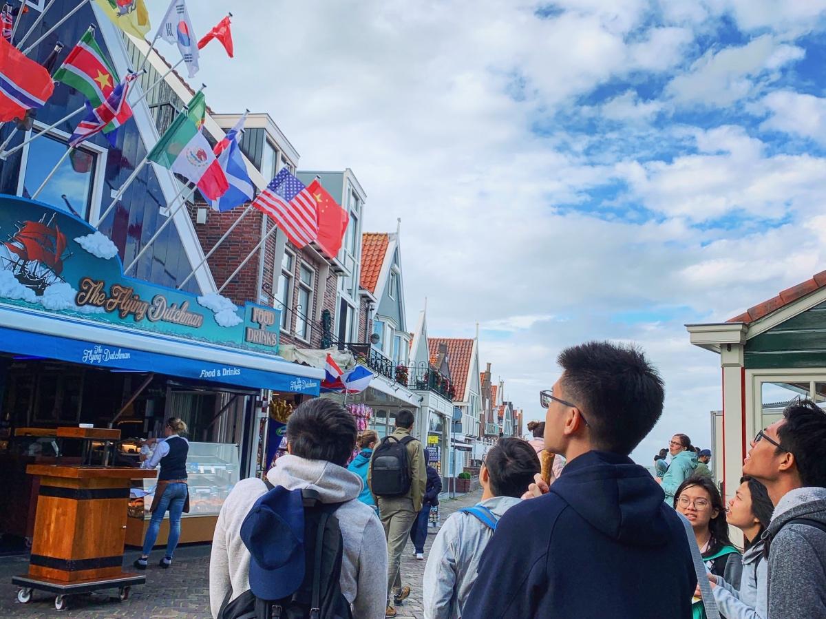 Aziatische toeristen die in Volendam een typisch Hollands huisje op de dijk staan te bekijken