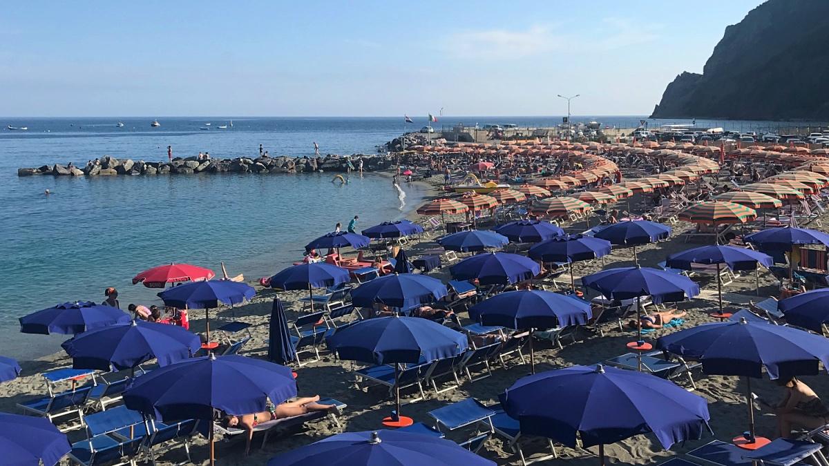Een strand vol met identieke parasols en ligbedjes voor het massatoerisme in Cinque Terre, Italie