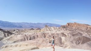 Toerist poseert op Zabriskie Point in Death Valley, Verenigde Staten