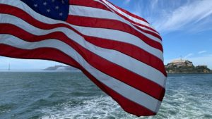 Wapperende Amerikaanse vlag op de ferry vanaf Alcatraz Island in de baai bij San Francisco met op de achtergrond het gevangenis eiland en de Golden Gate Bridge