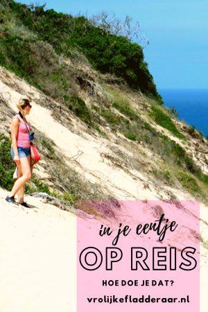 pinterest pin met de tekst 'in je eentje op reis, hoe doe je dat?' met een meisje in haar eentje in het buitenland op de achtergrond